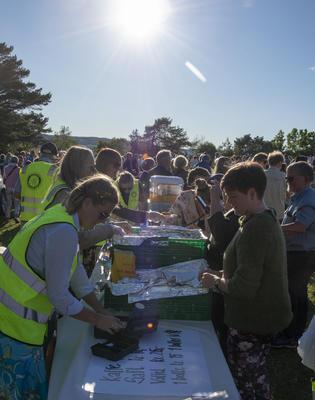 Frivillige fra Hamar Rotaryklubb står med gule refleksvester og selger kaffe og boller til publikum.