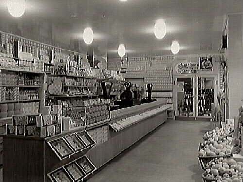 Interiör från Kooperativa föreningens butik med välfyllda diskar och hyllor. Till höger i bild syns korgar med frukt.