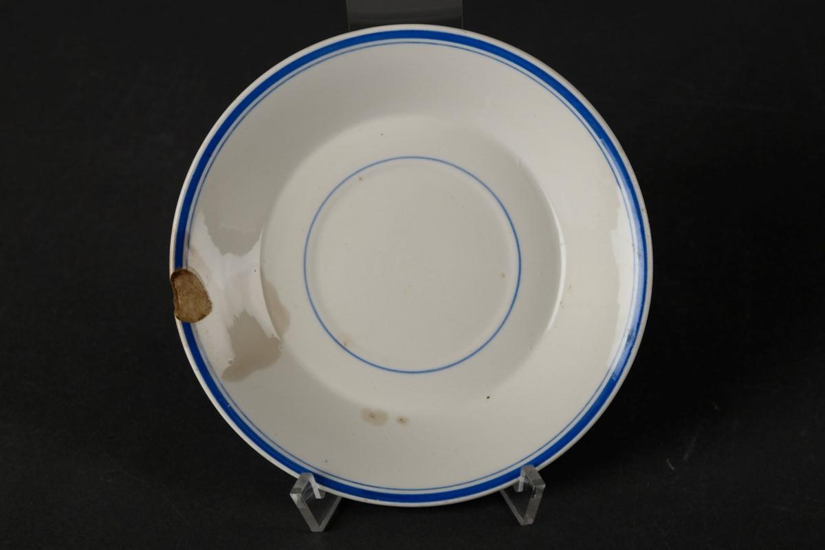Hvitt tefat med tre blå sirkler.