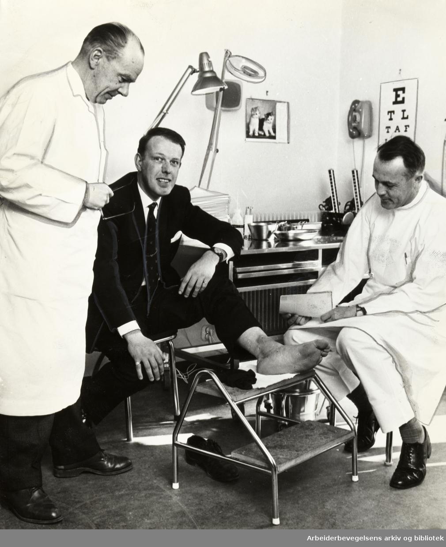 Legevakta. nr.2. Røde Kors- legevakta i Gabels gate. Direktør dr. med. Ragnar Nordlie, pasienten D. Sanderson fra Newcastle og behandlende lege drr. Einar Gjersøe. Mai 1966