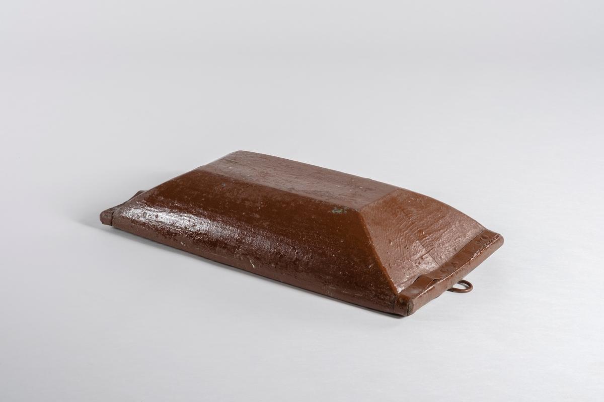 Dyp trau med kant i hver kortende som er beslått med metallbånd, og er skrudd fast. På den ene siden er det en jernhank festet med nagler. Det ser ut som trauet har vært malt grønt før det ble malt rødbrunt på utsiden.