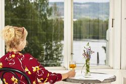 Dame i rød bluse som med ryggen til. Ser ut av vinduet ut mot elva.  Damen sitter på en stol og holder høyre hånd rundt et glass med eplemost som er plassert på et bord. En glassblomstervase med blomster (Foto/Photo)