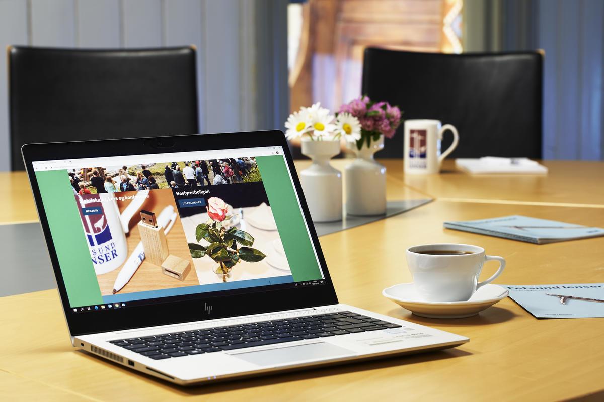 Bærbar pc i forgrunnen med kaffekopp og folder på høyre side på et konferansebord. Blomster og kaffekopper i bakgrunnen