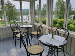 En glassveranda med to bord med blomster og stoler plassert rundt bordene. (Foto/Photo)