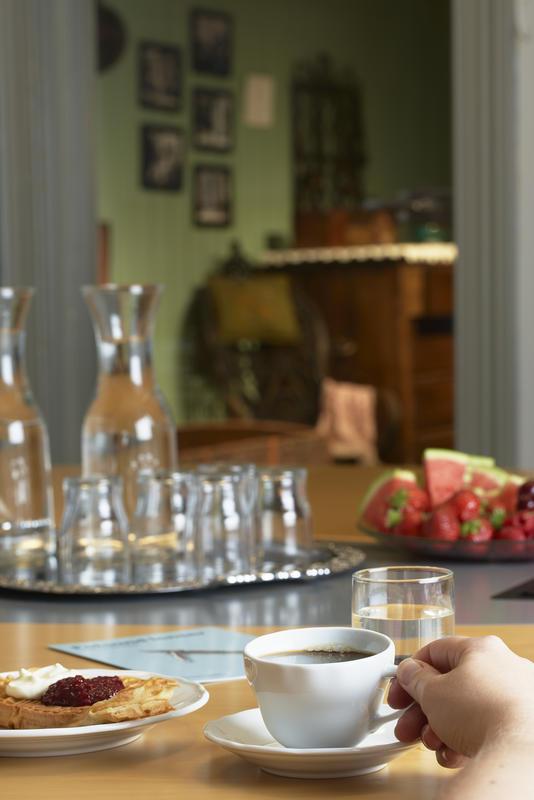 En hånd som holder i en kaffekopp ved siden står en asjett med vaffel. I bakgrunnen står et frukt fat og karafler med vann og tilhørende glass.