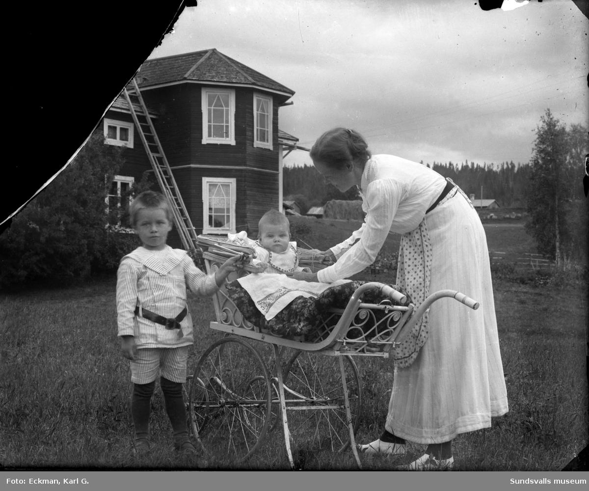 Fotograf Karl Eckmans fru Hildur med de bägge sönerna Robert och John (John i vagnen). Huset ligger vid Kvarnån, som rinner ut i Indalsälven mellan Glömsta och Micksäter. Glasnegativet är trasigt och det saknas en bit. Ur Karl Eckmans samling.