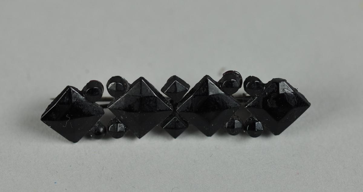 Svart brosje, sannsynligvis av bakelitt. Består av fire fasseterte romber på rad, med små dekorrundinger mellom.