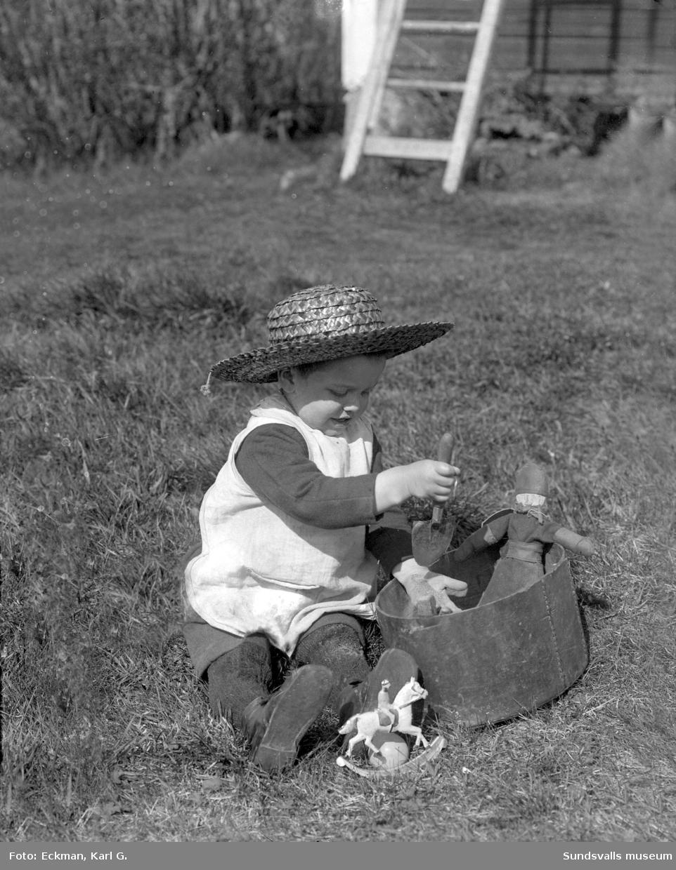 Ett barn, möjligen Rakel eller Ulla Eckman, med halmhatt leker med sand och en spade med docka och leksakshäst intill. Ur fotograf Karl Eckmans samling.