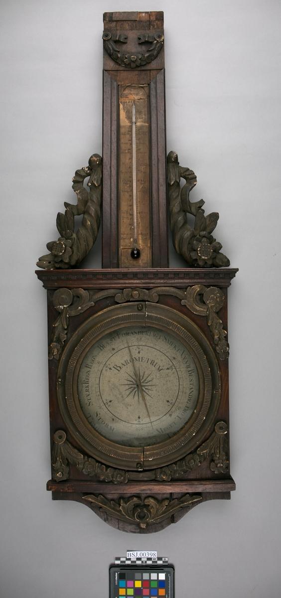 Barometer og termometer. Vegghengt aneroidbarometer med termometer montert på rikt dekorert mahogny plate med utskjæringer.