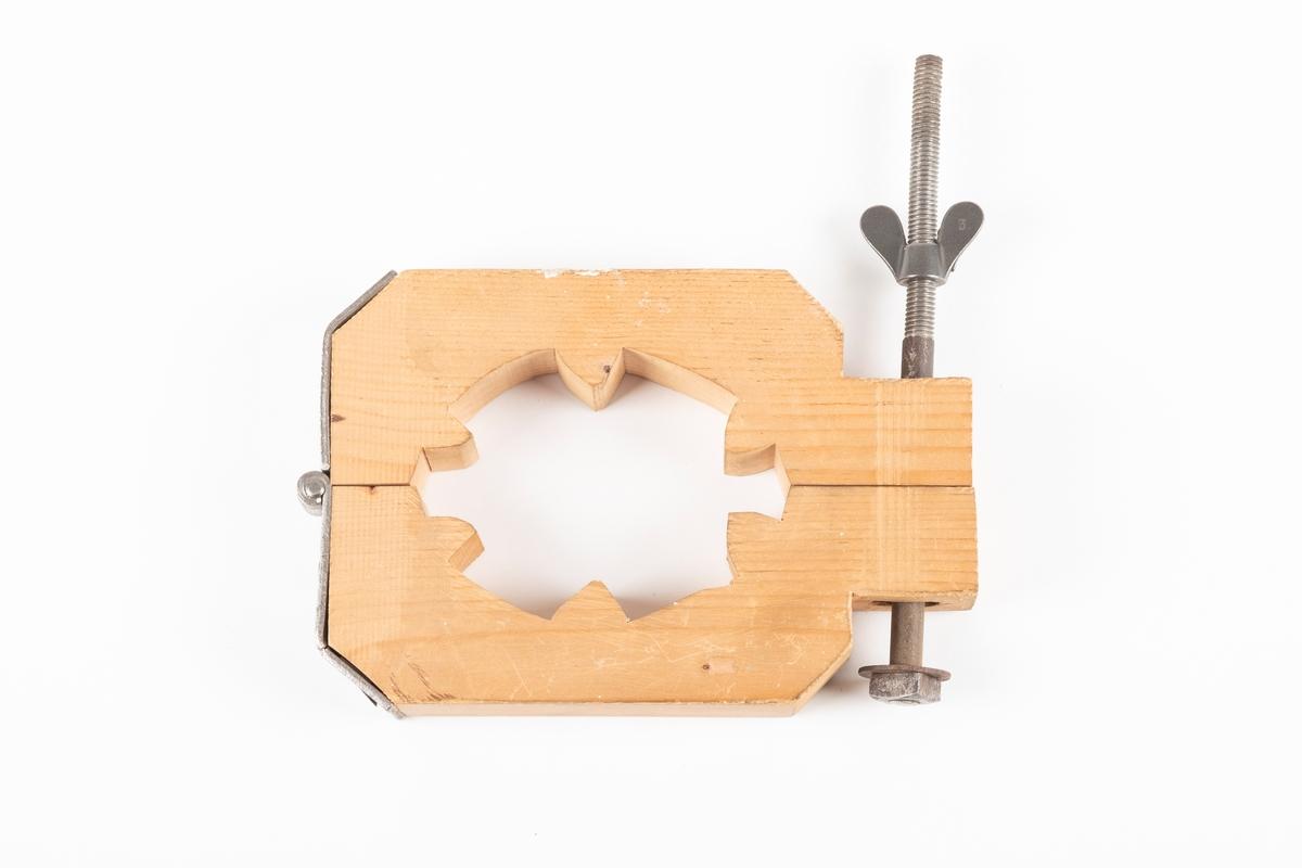 En kopi av en fotklemme av tre og metall. Fotklemmen åpnes og lukkes på den ene siden med en skruebolt med mutter. På den andre siden er det hengsel. Fotklemmen er skåret ut, og hullet i midten der foten klemmes er skåret ut med spisse topper.