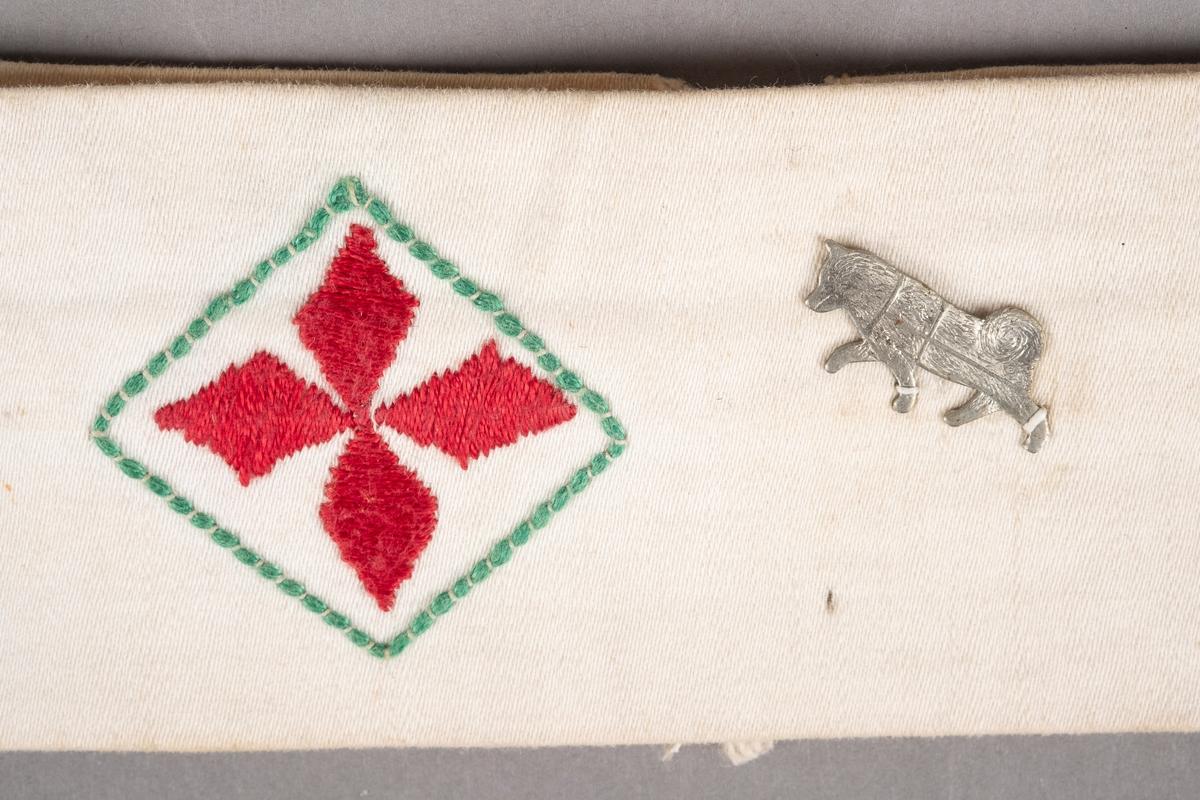Et armbind i hvit bomull med rødt kors brodert i midten. Ved korset er det påsydd et merke av en hund.