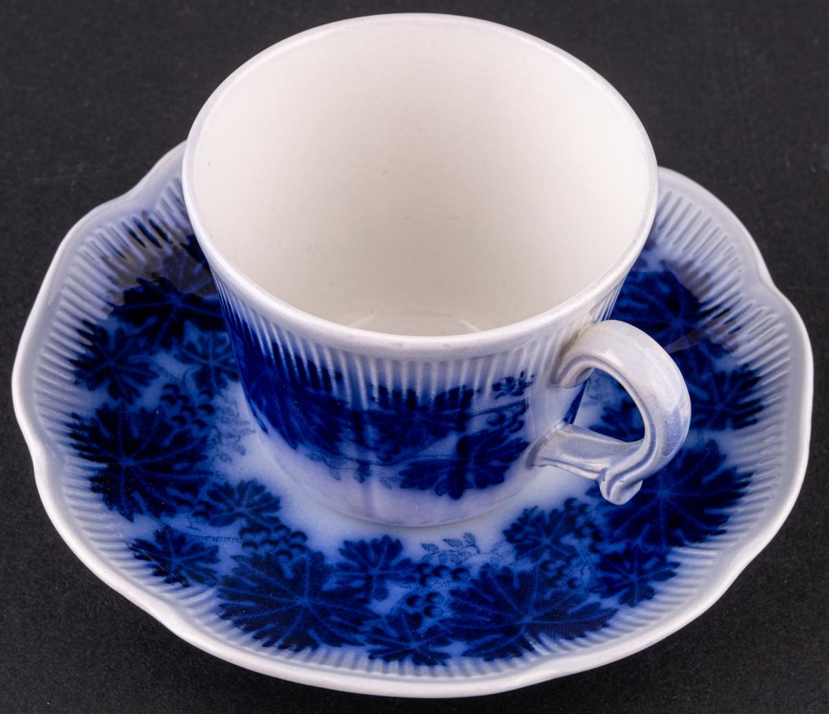 Kaffekopp med fat, modell AO i dekoren flytande blå Vinranka. Vinlövskrans runt kopp och fat, koppen är räfflad upptill och fatet har räfflor runt det något vågiga brättet.