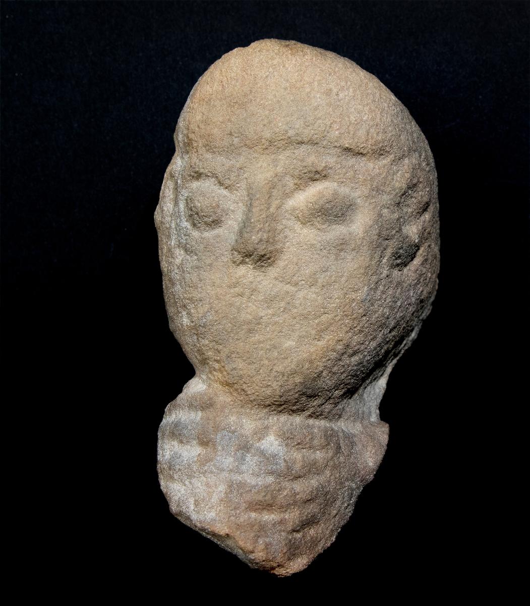 Skulpterat huvud av sten.