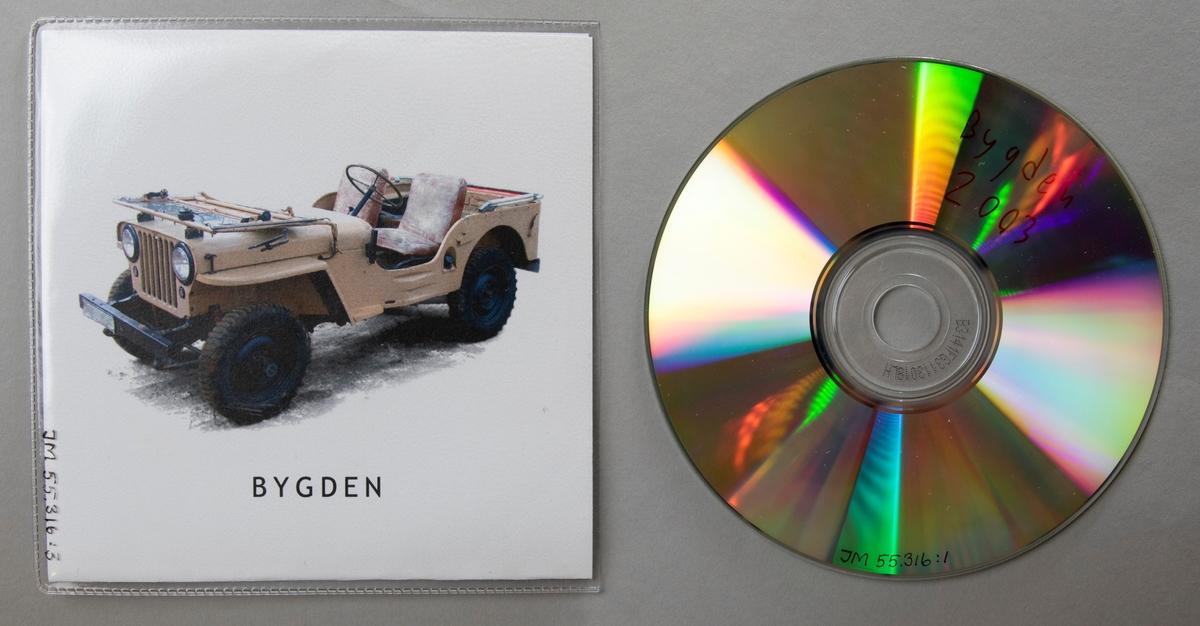 CD-skiva, musik med gruppen Bygden. Skiva i fodral av vikt pappersark i plastficka. Framsidan har ett fotografi av en beige bil (jeep-typ).  Innehåll: 1. Malte Mex 2. Iskallt uppdrag 3. Ljus i mörkret 4. Som en maskin på kneget  JM 55316:1, Skiva JM 55216:2, Fodral, vikt papper JM 55316:3, Fodral, plastficka