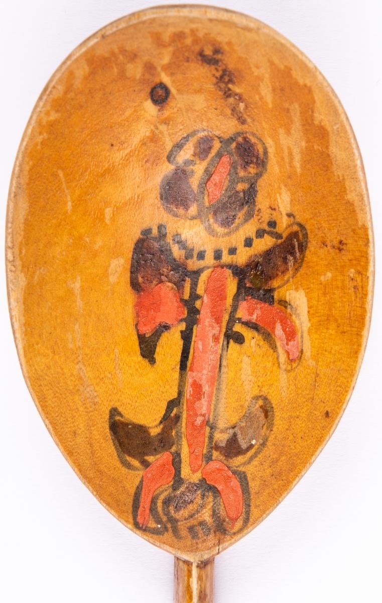 Träsked, rak form med kort skaft. Gulbrun grundfärg och blommotiv i svart och rött på bladet. Brännmärkt; HB