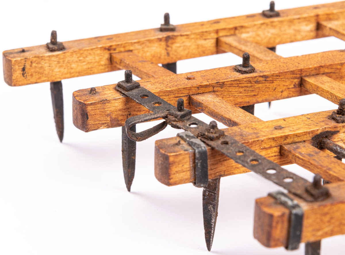 Modell till dubbelharv, åkerbruksredskap.  Pinnharv med 40 stycken raka järnpinnar, fästa i träbakjar. Fyra träbalkar med slåar. De två harvdelarna sammahållas genom två hophakade rundjärn. Modellens totala längd 26 cm, bredd 16 cm.