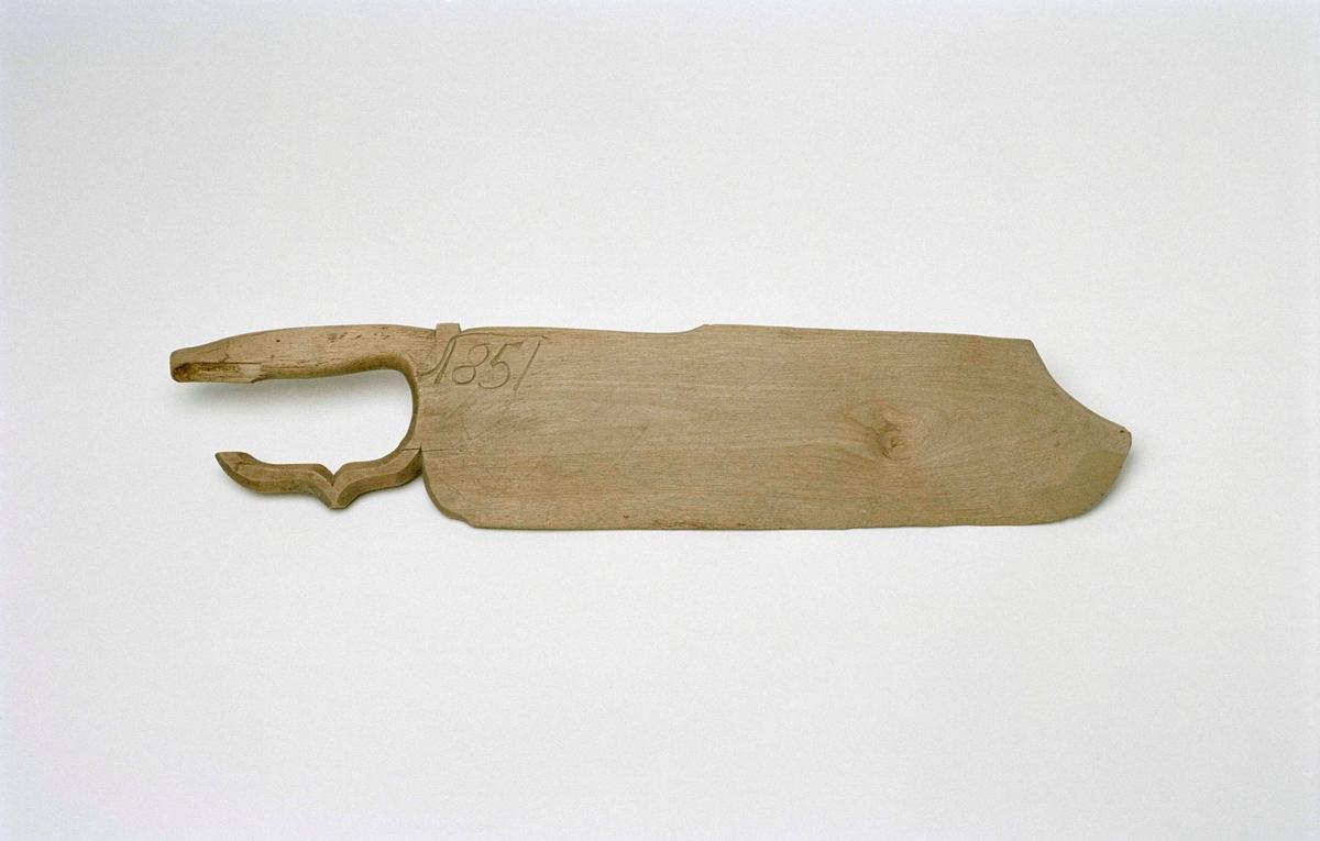 """Skäktträ av omålad björk med långsmalt blad och profilerat sabelfäste till handtag. Bladet i stort sett jämnbrett, avslutningen mjukt spetsig, halva spetsen insvängd. Inristat """"1851"""" samt vid sabelfästet ett """"X"""". Svagt inristade siffror på bladet, likt uppställda siffertal."""