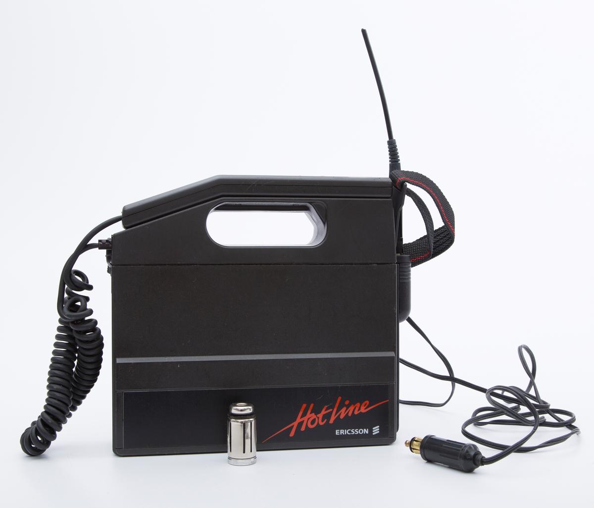 """Mobiltelefon i plast og metall, sort. Firkantet boks med telefonrør og bærerem. Mrk:""""Ericsson"""". """"Hotline"""".  A:Radioenhet  B: Nettenhet  C:Telefonrør D:Antenne E:Rørholder F:Batteri G:Adapter H:Sigarettenner - lader I:Bærerem J:Instruksjonsbok K:div.papirer"""
