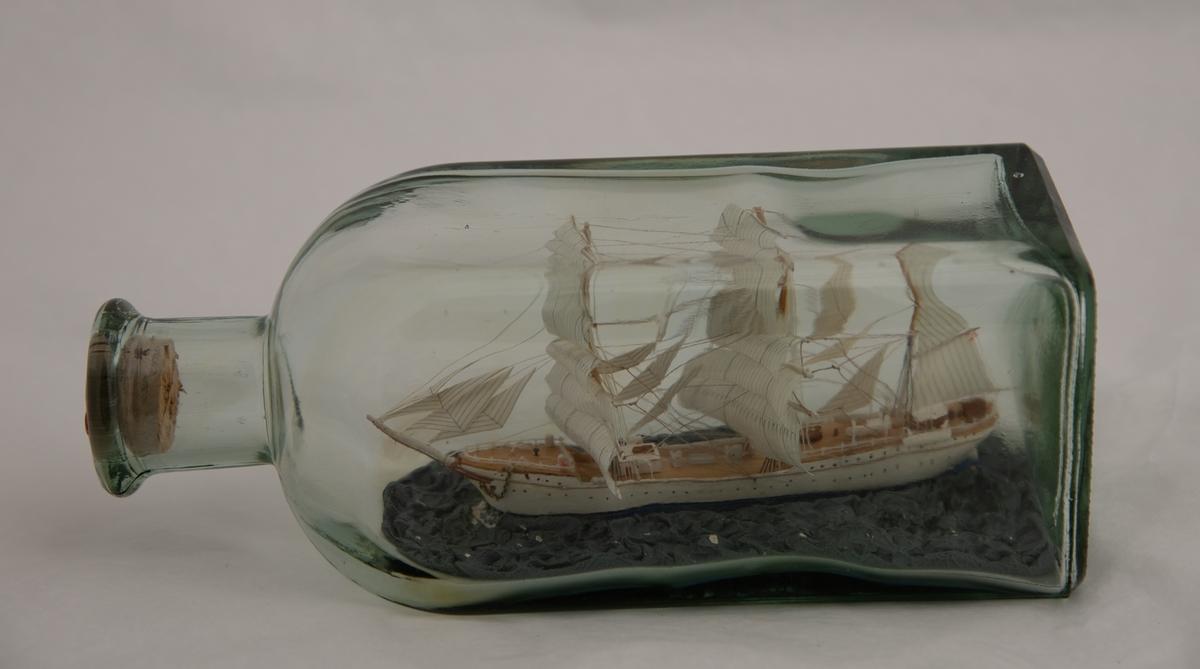 """Skoleskipet """"Statsraad Lehmkuhl""""   Bark med hvitmalt skrog , hvite seil , langt , slankt skrog. Blå sjø."""