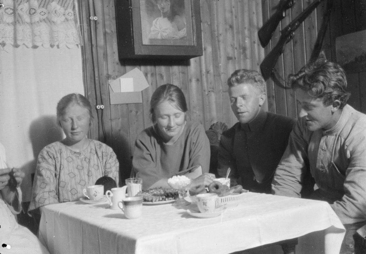 To par ved kaffebord med kaker. Brystbilde av dame på veggen, samt geværer.