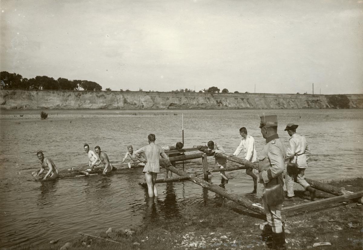 Elever från Krigsskolan Karlberg bygger bro över vattendrag.