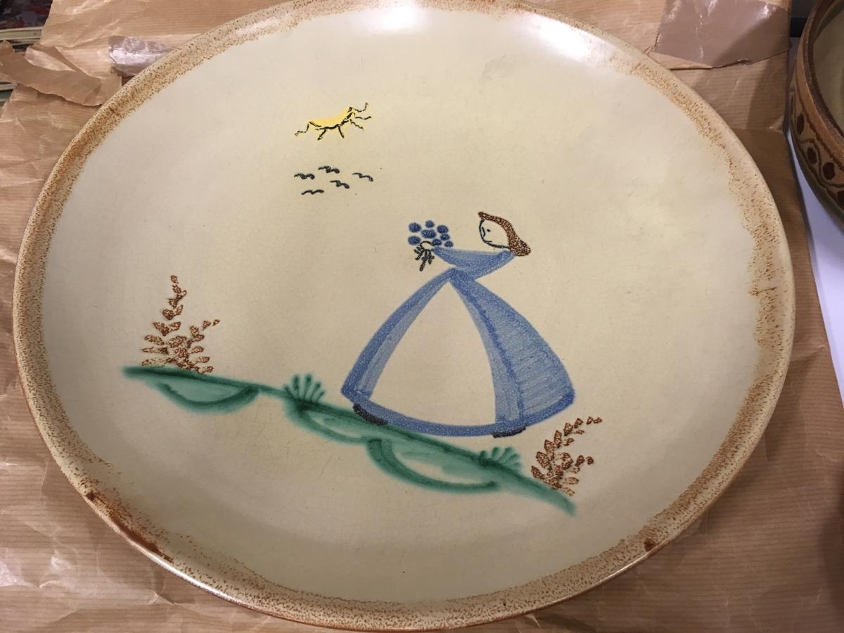 """Pike i blå kjole med blomsterbukett, på grønn """"plen"""". 5 stiliserte måker og gul sol."""