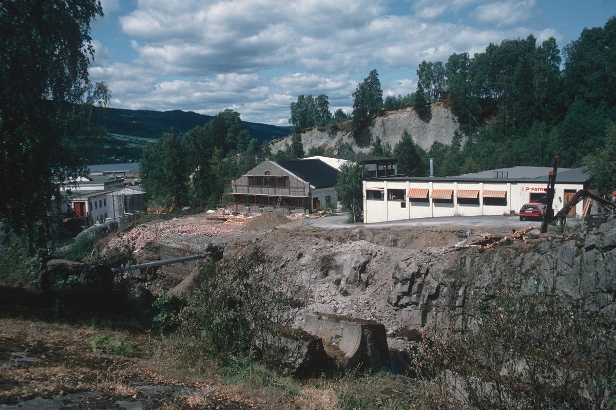 Lillehammer.  Utgraving for Mesnadalsvegen nedenfor tunnelen.  Gamle Knappfabrikken og Lill-Sport bak gropa. Søndre del av Knappfabrikken er revet.  Kværner Mesna A/S t.v.  Sett mot nord-vest.