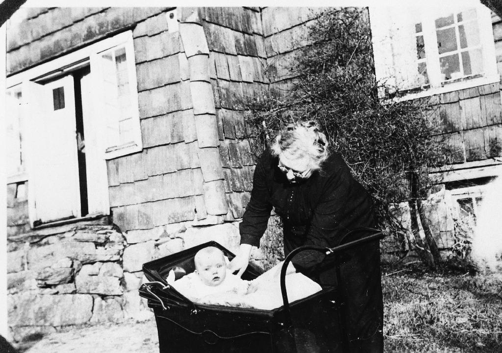 Grete Aasland med barnebarnet Ingfrid Håland i vogna framfor det pannekledde huset på Lindland.