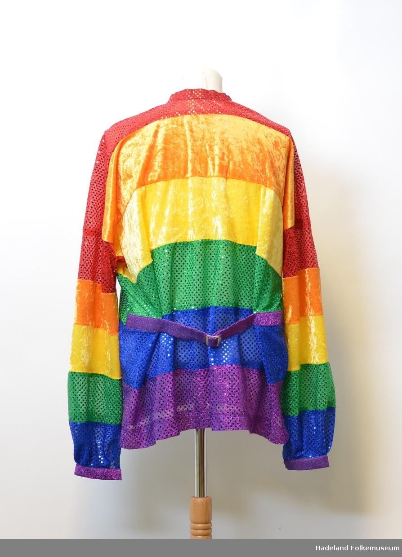 Skjorte i busserull-fasong sydd i regnbuefarget paljettstoff og fløyel. Dekorert med kirsebær- og leppe knapper, samt spensel i ryggen.