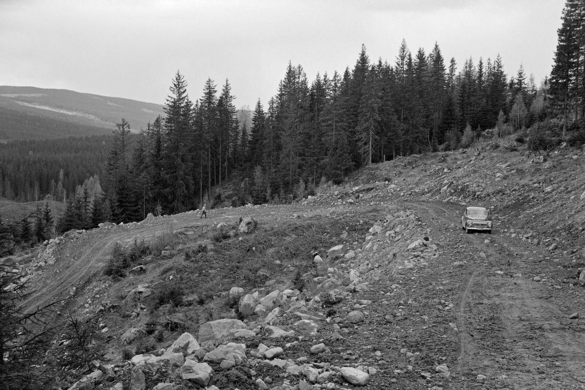 Nybygd skogsbilveg i Hurdal i Akershus, sannsynligvis fotografert i 1962. Fotografiet er tatt i ei forholdsvis bratt li, der vegbyggerne har måttet lage en forholdsvis krapp sving for å oppnå akseptable stigningsforhold. Prosjekteringa av slike veger skulle nemlig baseres på en serie økonomiske kalkyler, og bratte bakker betydde lavere kjørehastighet, mindre lassvolumer, høyere dieselforbruk og mer slitasje på transportmateriellet. I tillegg hadde smelte- og regnvannet større erosjonskraft i bratte bakker enn i mer slakt terreng. Dette var viktige årsaker til at denne vegen ikke ble lagt rett oppover den forholdsvis bratte lia. For å få akseptable stigningsforhold måtte man akseptere en annen ulempe – forholdsvis krappe svinger. Mellom svingene skulle det helst være rette strekninger av en viss lengde, og kurvene måtte ikke bli for krumme. En regel sa at tangentlengden – avstanden fra kurvens startpunkt til skjæringspunktet mellom to tenkte linjer i forlengelsen av de rette partiene på hver side av svingen – burde være minst 25 meter. Dette fotografiet illustrerer også to andre momenter som var viktige ved prosjektering av skogsbilveger: I skrånende terreng skulle en gjerne legge vege på naturlige hyller i terrenget, noe vi ser er gjort til venstre i dette bildet, og vegene skulle fortrinnsvis bygges av stedlige masser som en i skrånende terreng hentet fra vegens innside og la som fylling på utsidene, noe vi kan observere til høyre her. Da dette fotografiet ble tatt sto det en personbil – en Volvo PV – parkert på den fortsatt bare grovplanerte vegbanen til høyre i bildet, og en mann gikk i svingen bakenfor.