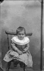 Jente, anttatt 2 år som sitter på en pinnestol, kledd i møns