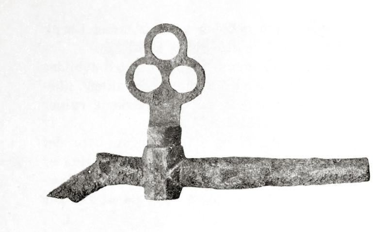 """Tverrgående metall""""pinne"""" med liten knekk ned på venstre side. Nokså langt ute til venstre på """"pinnen"""" (som er hul) sitter en slags ventil med et trekløverformet håndtak."""