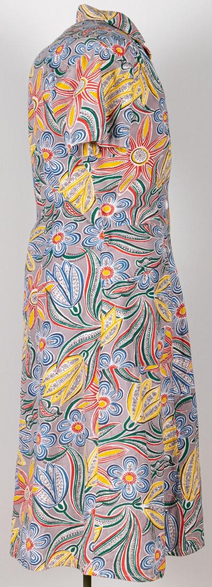 Städrock med kort ärm och krage, ok framtill. Påsydda fickor, knäppnig fram med 8 vita knappar 1 olik de andra. Stilserat blommönster i rött, blått, gult, grönt och grått. Tryckt på vit botten. Märkt Sjömans. Stl 42. Tillverkad av Sjömans.