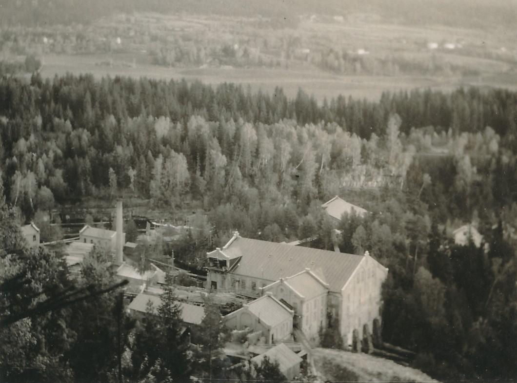 Fabrikkområde med industribygninger sett ovenfra. I bakgrunnen ser man skog og jordbrukslandskap.