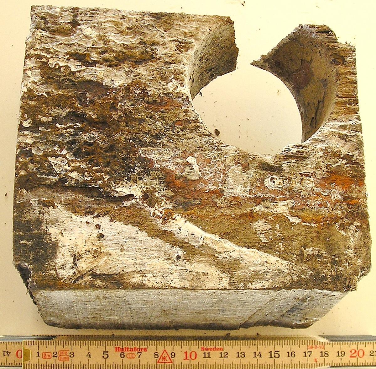 Utsågad del av bordläggningsplanka.  Biten har fyra borrspår och ett stort genomgående hål från tidigare dränering.