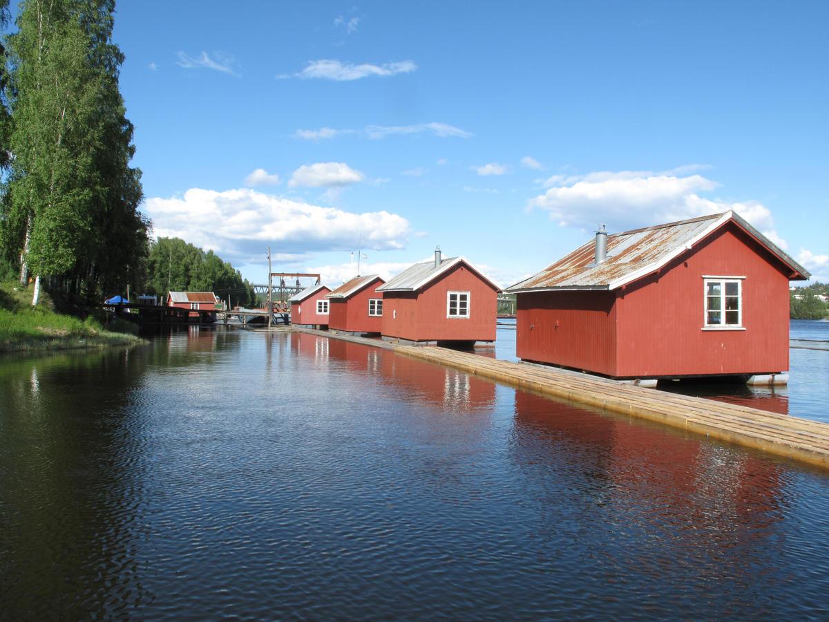 Fire røde små hus på vannet som ble benyttet som hvilebrakker da fløtingsanlegget var i bruk.