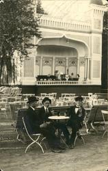 Vykort med motiv över tre sittande unga herrar vid musikpavi