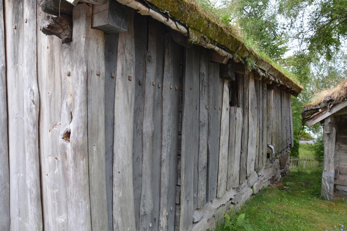 """Tømra bygning i eit rom med framrom i grindverk og ståande kledning.  Trørrmur grunnmur. Taket var opphaveleg tegl, men fekk torv på museet.   Båsar - veggane hadde tydelege merke etter båsar på begge sidene. 8 båsrom på eine sida, """"kanskje eit par færre på hi"""" (Arne Berg).  I gavlen er det ei lita dør til å kaste møk gjennom, """"møkedungsdøra""""."""