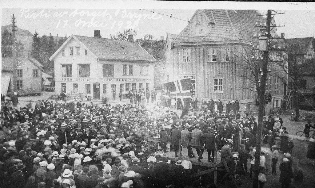 Prospektkort frå Torget på Bryne 17. mai 1921. Til v. forretningen til Johs. Ruud og til høgre Svein Tjemsland sin.