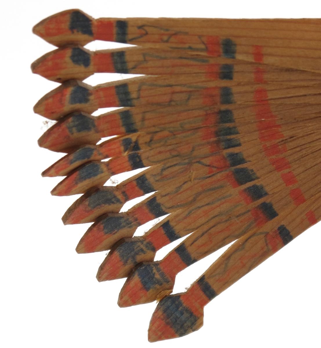 Sponfugl, laget av to stykker tre som er splittet opp til vinger og haleparti, og tilskåret som fuglens hode. Malt med vannfarger.