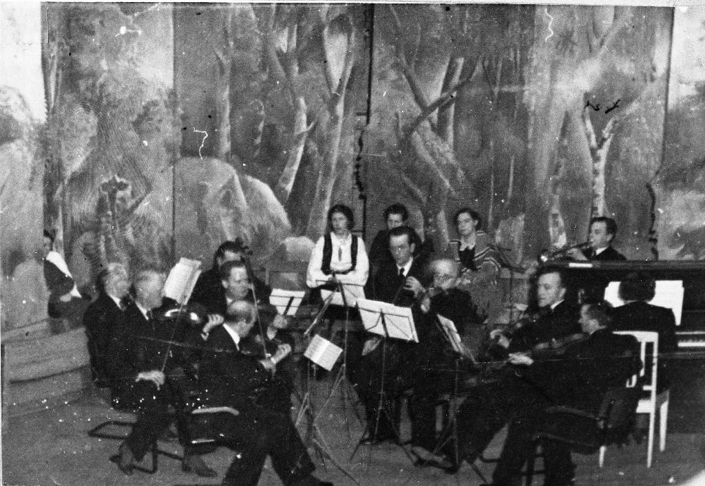 Juletrefest på Festiviteten for mannskoret og orkesteret Crescendo som Magnus Jonsbråten var leiar for. Biletet er teke frå galleriet og kulissane var faste og brukt til alle tilstelningar. Frå v. Johannes Ruud (fløyte), Johs. Eide (fiolin), Laurits Hareland (fiolin), Olav Stangeland (fiolin), Jens Laland (bakanfor med cello) Songsolistane som sit i bakgrunnen er : med bunad Kristina Takle Stangeland, halvt gøymd Astrid Svendsen og Gudrun Laland. Midt i biletet ved notestativet : Olav Line (cello), Magnus Jonsbråten (bratsj), A. K. Fylling (fiolin), Mons Houge (fiolin), ved pianoet Ingeborg Laland og bak Arne Nagel-Dahl (trompet).