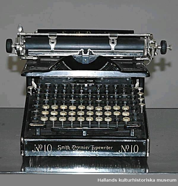 """Märke: """"No. 10 Smith Premier Typewriter."""" Tillverkad i USA. Tangenter dels för stora, dels för små bokstäver samt för siffror och andra tecken. Svartmålad med guldskrift."""""""