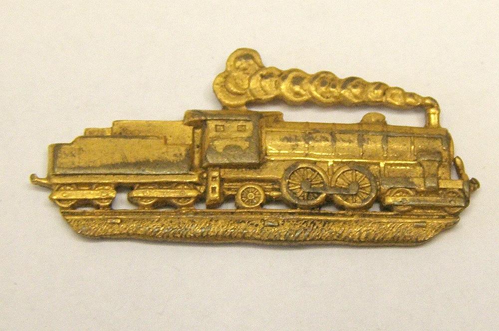 Rockslagsmärke i form av ett ånglok med tender i guldfärgad metall. Loket är på väg till höger.