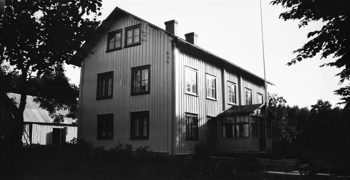 """""""Tranebergs hus, Varberg."""" Ett stort timrat tvåvåningshus med glasveranda, vid vars gavel en flaggstång är fästad. Elledningar löper från husets gavel och i bakgrunden skymtar en ladugård. I förgrunden står trädgårdsmöbler."""