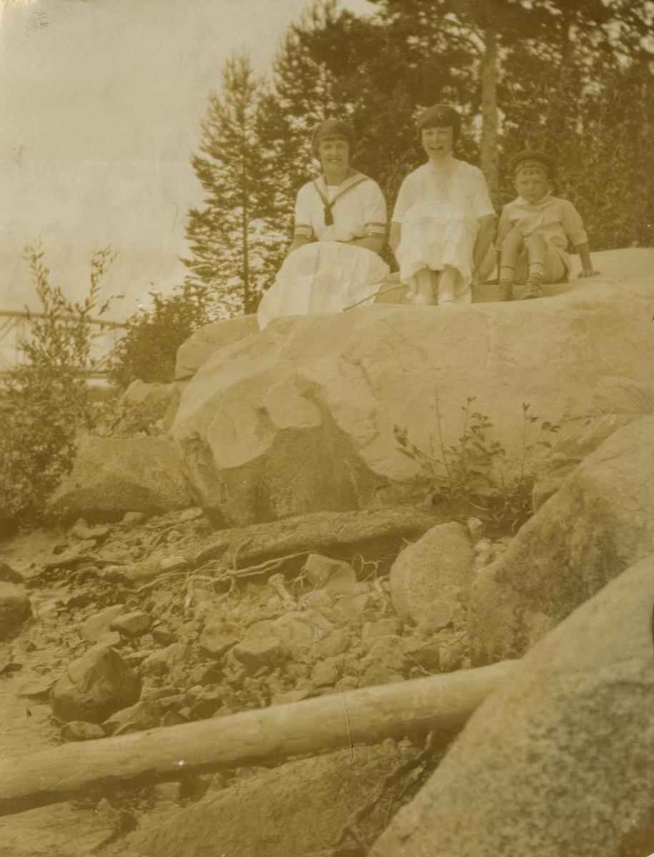 Barn sittandes på en stor sten.