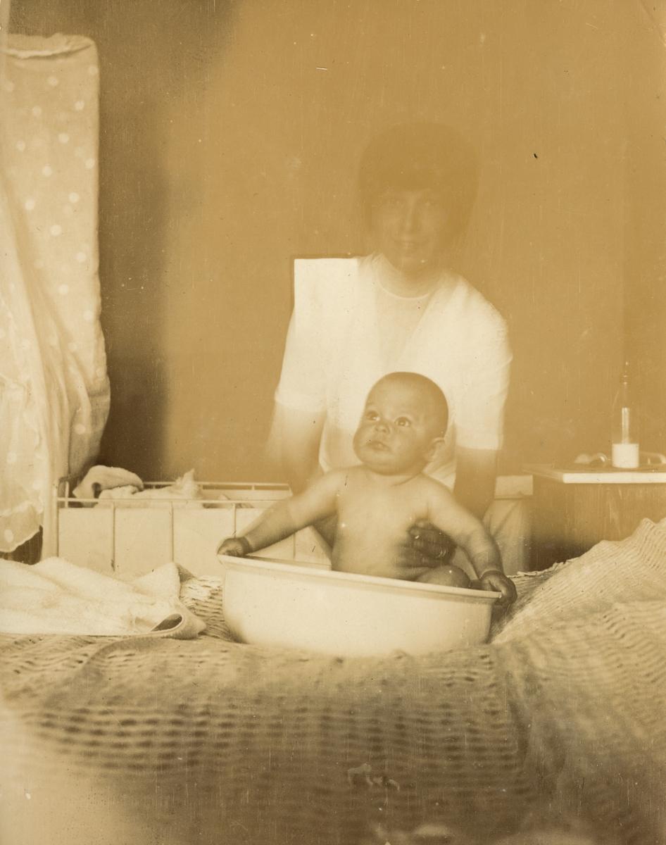 Porträtt på kvinna med barn.