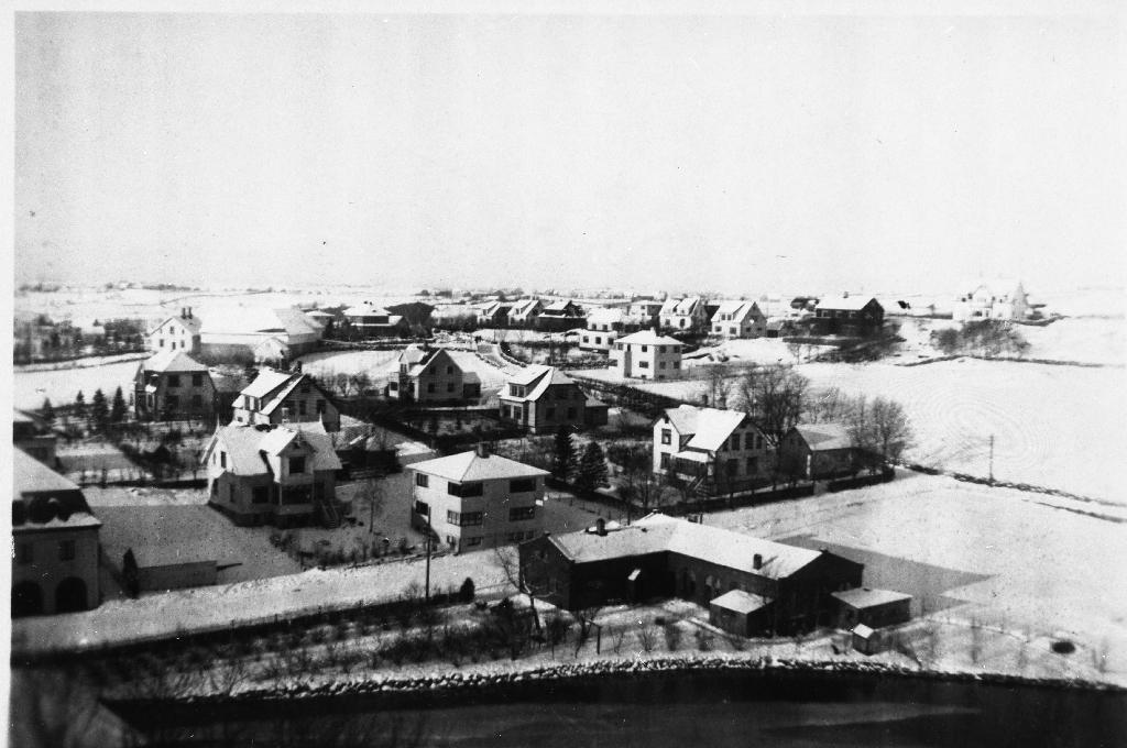 """Frå nordre del av Bryne mot vest. I framgrunnen Bryneånå og Time Trevare. Til v. ser vi litt av Festiviteten, så huset til Haugstad, så tannlege Magnussen og """"Klosterhagen"""". I bakggrunnen til høgre ser ein Fødeheimen."""