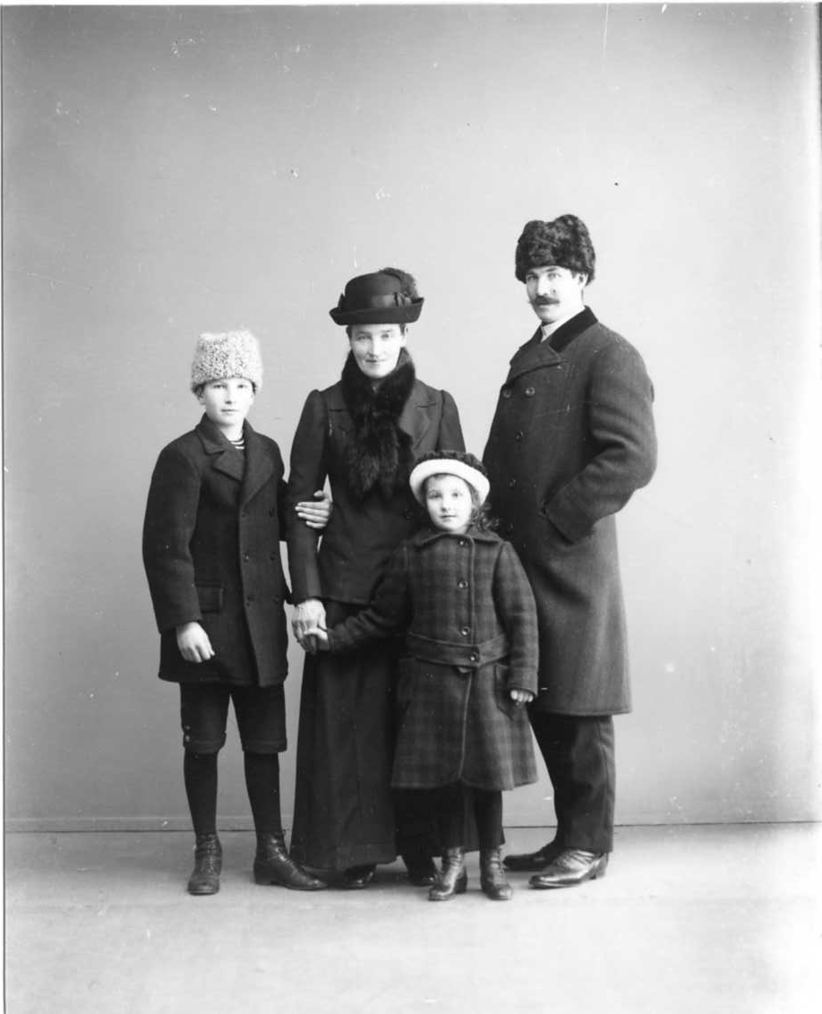 Gruppbild med familjen Karlsson, vinterklädda med huvudbonader i ateljén. Hugo Karlsson håller vänster hand om mamman Anna Karlssons högra arm. Hon håller i samma hand dottern Gretas hand. Till höger står pappan Oskar Karlsson.
