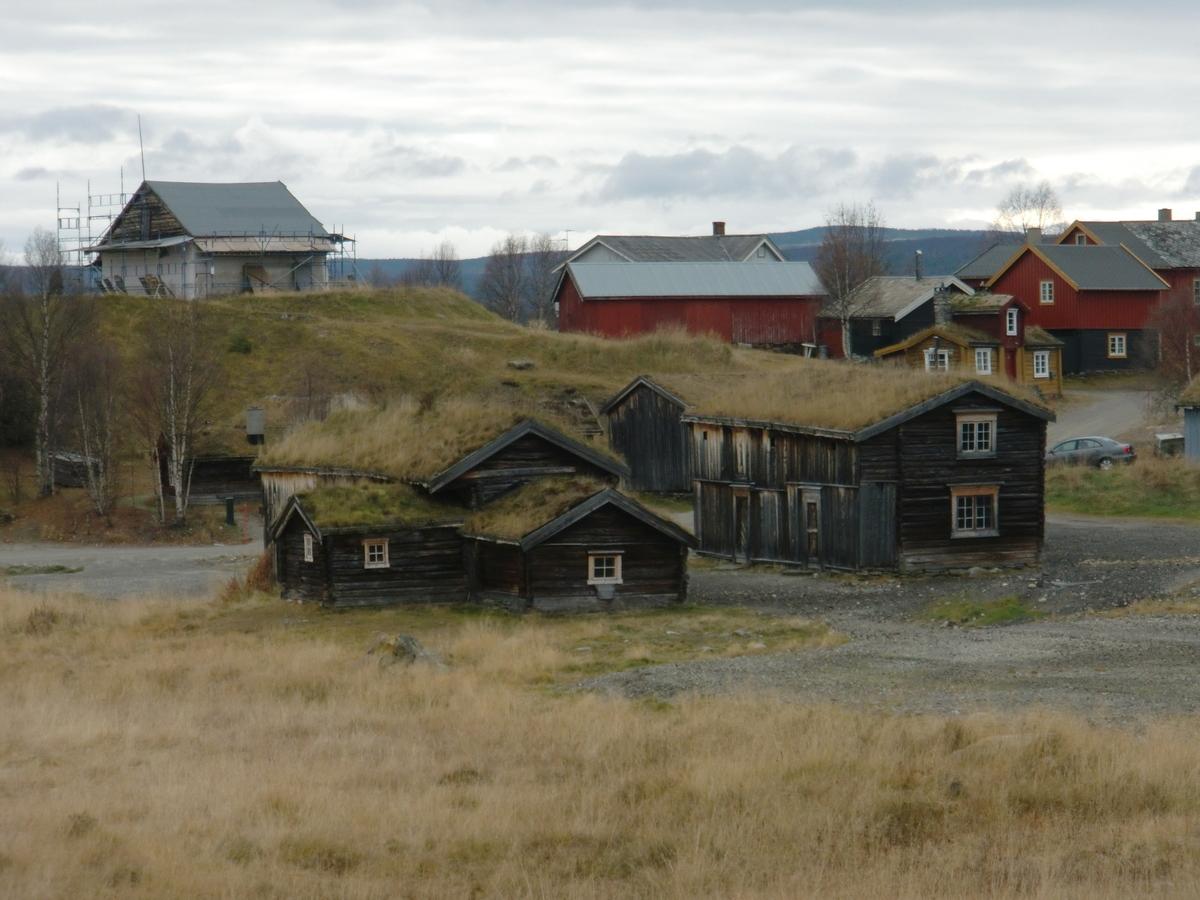 To-etasjes bygning av laftet tømmer og langsval av bindingsverk. Torvtekket tak.