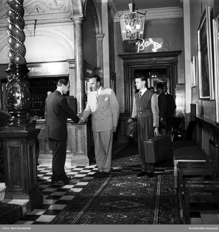 Gunnar Wilöf hälsar artisten Charlie Norman välkommen till hotell Knaust. En piccolo väntar med väskorna.